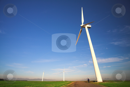 Wind powered turbine stock photo, Wind powered electricity generator standing against the blue sky in a green field on the wind farm. A man is walking past the first generator by Sean Nel