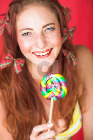 Female Fashion Model stock photo, Young female adult fashion model with natural red hair and freckles in a yellow bikini with a big multi-colored lollipop (textured red faux leather background) - Very Shallow Depth of Field by Sean Nel