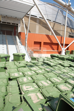 Rubbish bins stock photo, Stacks of green rubbish bins standing outside a sports stadium. by Sean Nel