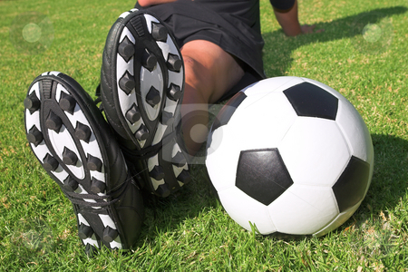 Football player with a soccer ball on soccer pitch stock photo, A male soccer (football) player, referee or coach sitting next to a soccer ball. The image is of feet and legs, with soccer togs, and a black and white ball. Focus on soccer ball and heels by Sean Nel
