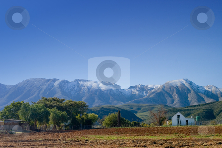 Farm #1 stock photo, Farmhouse behind newly plowed field - Snow covered mountains in the background - De Rust, South Africa by Sean Nel