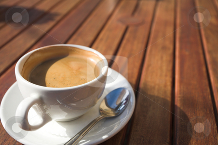 White coffee cup on wooden table stock photo, White coffee cup with rich coffee and foam on a brown wooden table  by Sean Nel