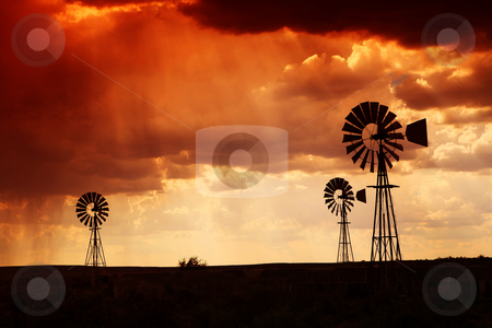 Rain in the dessert at sunset stock photo, Brewing thunderstorm in the dessert area of the Karoo in South Africa just before sunset. Three wind pumps silhouetted against the skyline with sunbeams shining through the clouds. by Sean Nel