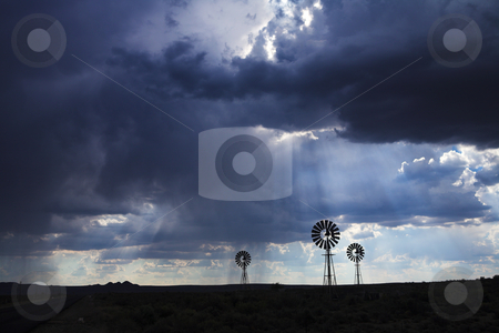 Rain in the dessert  stock photo, Brewing thunderstorm in the dessert area of the Karoo in South Africa. Three wind pumps silhouetted against the skyline with sunbeams shining through the clouds. by Sean Nel