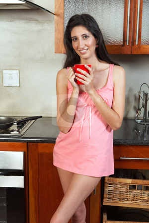 Sexy brunette woman stock photo, Sexy young adult brunette woman in lingerie drinking morning coffee in her kitchen before work by Sean Nel