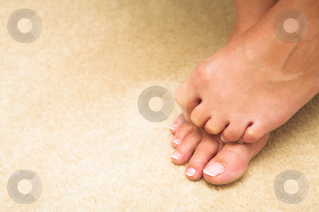 Woman hiding toes stock photo, Feet and toes of a young adult woman. She is hiding her toes and curling them up. by Sean Nel
