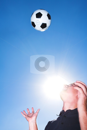 Soccer player or coach and ball against a blue sky stock photo, A male soccer referee or coach catching a soccer ball. He is wearing a black shirt and the sun is shining from behind his face. There is movement on his hands and the ball but elements of the face is sharp. by Sean Nel
