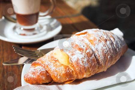 Early morning coffee and croissant  stock photo, A cup of coffee and fresh cream croissant on a wooden table in an outdoor cafe. Very shallow depth of field, focus on top of croissant by Sean Nel