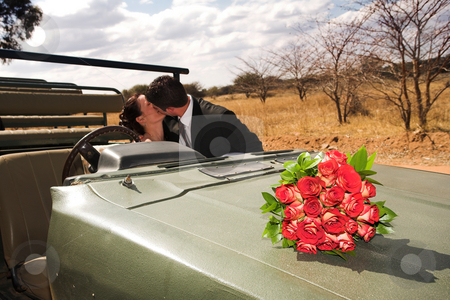 Bridal Couple #49 stock photo, Red bouquet of roses on the bonnet of a car, just married bridal couple kissing in the background. Focus on Flowers by Sean Nel