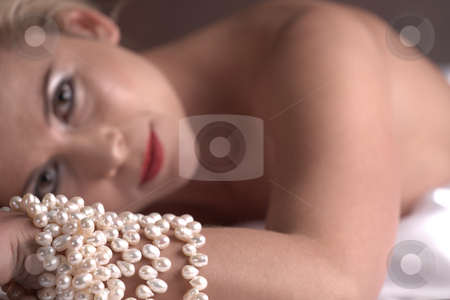 Nude adult woman stock photo, Sensual naked young blonde adult Caucasian woman, wrapped in a satin, silk sheet on a bed in her bedroom. High contrast lighting. Very Shallow DOF, Focus on the pearls by Sean Nel