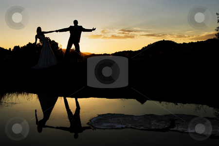 Couple #2 stock photo, Bride and groom next to river at sunset by Sean Nel