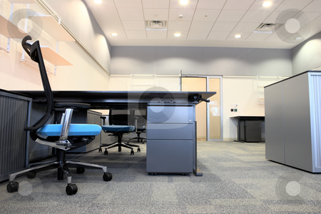 Interior of a new office stock photo, Empty office with new modern office furniture, including desks, cupboards, filing cabinets and chairs. Two blue chairs facing out. HDR type image by Sean Nel
