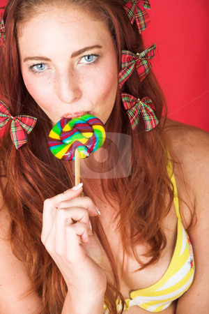 Female Fashion Model stock photo, Young female adult fashion model with natural red hair and freckles in a yellow bikini with a big multi-colored lollipop (textured red faux leather background) by Sean Nel
