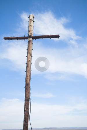 Wooden cross stock photo, Wooden cross with electric lights on the edges against a blue sky by Sean Nel
