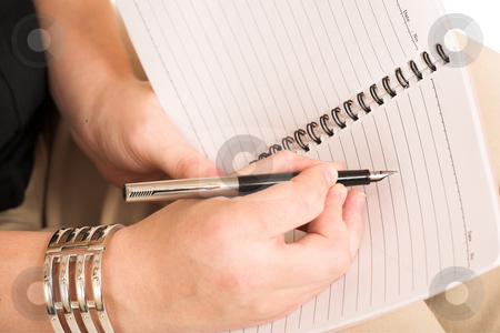 Business Woman #507 stock photo, Business Woman, wearing black top and beige pants, writing with pen in notebook by Sean Nel