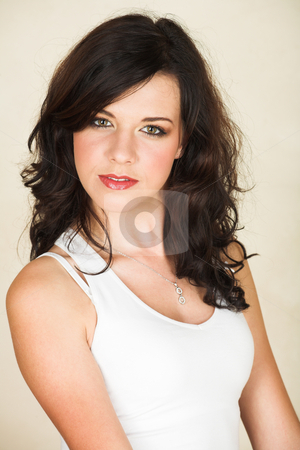 Young brunette woman stock photo, Young adult brunette woman with a white top and long brown curly hair and brown eyes looking at the camera and smiling by Sean Nel