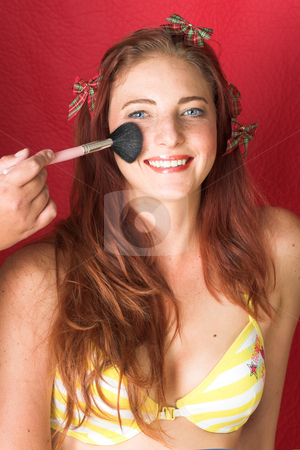 Female Fashion Model stock photo, Young female adult fashion model with natural red hair and freckles in a yellow bikini getting make-up (textured red faux leather background) by Sean Nel