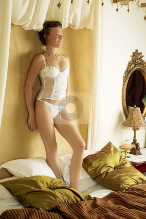 Lingerie#261 stock photo, Woman in underwear standing on a bed. by Sean Nel