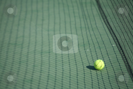 Tennis ball on a court stock photo, Yellow tennis ball on a green tennis court right next to the net by Sean Nel