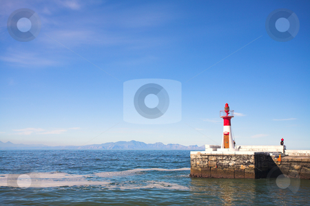 Harbor entrance lighthouse against blue sky stock photo, The left harbor entrance (red) lighthouse at Kalk bay harbor in the Western Cape, South Africa. A sunny summer day, with clear blue skies and calm water. by Sean Nel