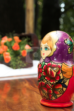 Red and purple stacking doll stock photo, Traditional Russian red and purple nested doll or stacking doll (matryoshka) on a table with flowers in the background by Sean Nel