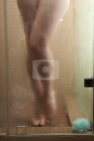 Woman in Shower stock photo, Sexy young adult Caucasian woman with long auburn hair and petite breasts taking a shower in a tile and glass modern bathroom. Part of a series. by Sean Nel