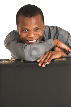 Businessman #140 stock photo, Businessman in grey shirt, leaning over a black leather suitcase, smiling. by Sean Nel