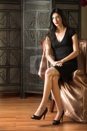 Italian adult woman stock photo, Beautiful young sexy adult Italian woman with long black hair, in formal black dress on a textured wooden background, sitting on a luxurious couch ? Hard light, high key by Sean Nel