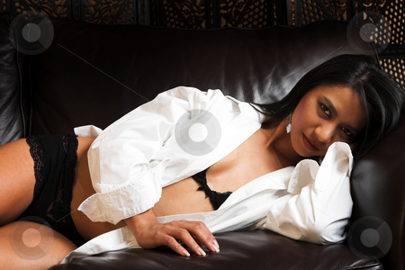 Sexy Indian woman in Lingerie stock photo, Sexy adult Indian woman in black lace lingerie lying on a brown leather couch with a white long sleeve shirt over her shoulders. by Sean Nel
