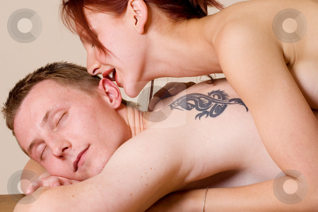 Couple #24 stock photo, Woman on the back of her boyfriend, whispering in his ear by Sean Nel