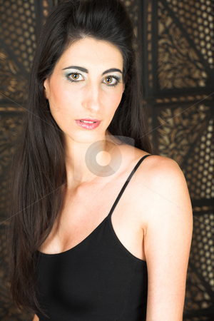 Beautiful young Italian woman stock photo, Beautiful young adult Italian businesswoman with long black hair, and a small black top on a textured wooden background by Sean Nel
