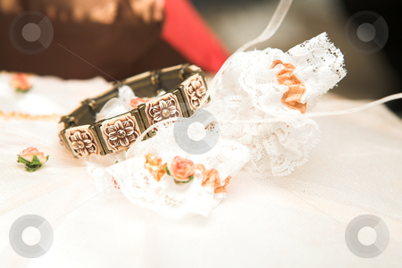 Bracelet and Garter stock photo, Brown flower bracelet and lace bridal garter lying on a bed  by Sean Nel