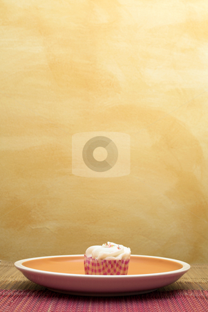 Cupcakes #4 stock photo, One Cupcake on pink and brown table cloth in front of  wall - copy space by Sean Nel