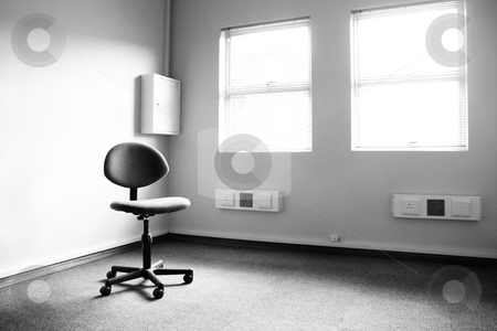 Lonely Chair stock photo, Black and white image of a single office typist chair in an empty office by Sean Nel