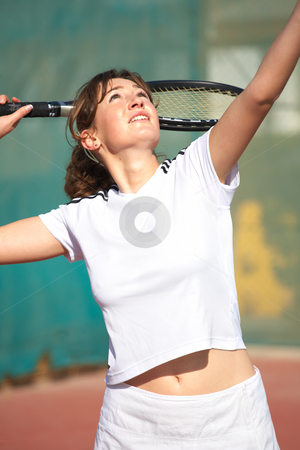 Female Tennis Players stock photo, Young woman playing tennis in the sun. About to serve the ball by Sean Nel