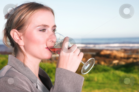 Woman drinking wine next to the ocean stock photo, Young blonde Caucasian woman drinking wine next to the ocean wearing a business suit by Sean Nel