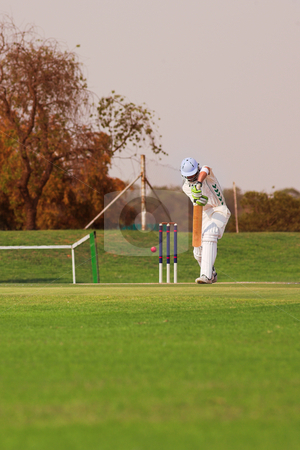 Cricket player hitting ball stock photo, Cricketers playing in the late afternoon, Batsman hitting ball on green cricket pitch - Overcast Day, before the storm by Sean Nel