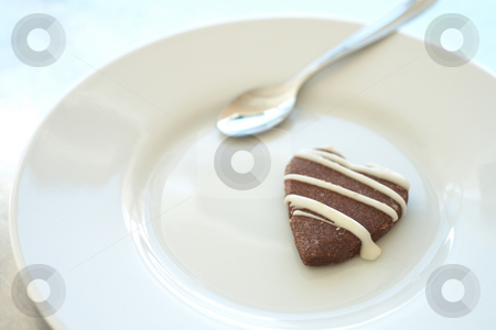 Cookie on a plate stock photo, The last cookie on a white ceramic plate with a silver teaspoon - Shallow Depth of Field, focus on the tip of the cookie by Sean Nel