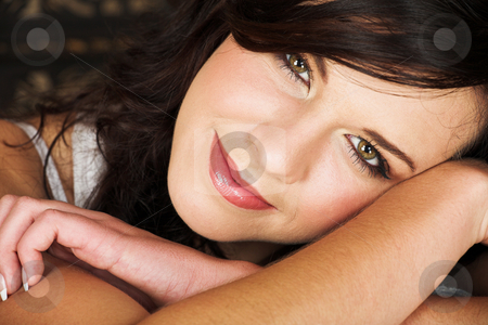 Young brunette woman stock photo, Young adult brunette woman with a white top and long brown curly hair and brown eyes lying on her arms and smiling at the viewer by Sean Nel
