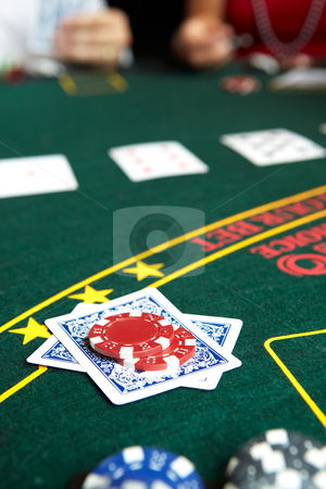 Card gambling stock photo, Playing cards, chips and players gambling around a green felt poker table. Shallow Depth of field, focus on the chips and folded hand. by Sean Nel