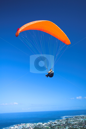 Paraglider launching from the mountain ridge stock photo, Paraglider launching from the ridge with an orange canopy against a blue sky. The town of Hermanus (Western Cape, South Africa) in the bottom of the image by Sean Nel