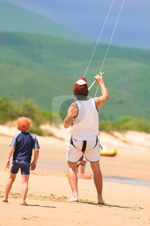 Kite surfer on the beach with a boy stock photo, A kite surfer is flying his kite on a sunny day at the beach at Plettenberg Bay, Western Cape, South Africa.  A small boy in a wetsuit is looking at him. Green mountains in the background and focus on the larger man. by Sean Nel