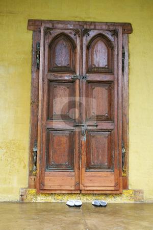 Old door stock photo, Shoes outside handmade door by Sean Nel