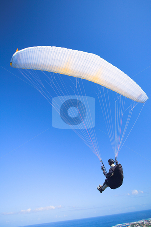 Paraglider launching from the mountain ridge stock photo, Paraglider launching from the ridge with a yellow and white canopy. The shot is taken right after takeoff. The canopy wingtip is sharp, with slight movement on the closer wing and the pilot by Sean Nel