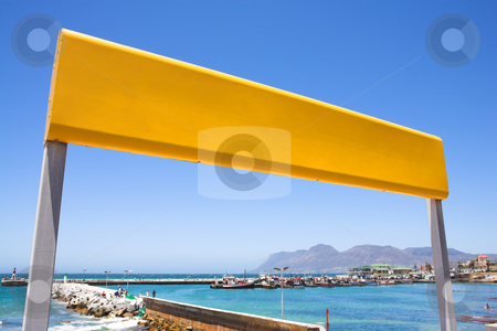 Yellow train station sign at the coast stock photo, Yellow train station sign against a blue sky with the Kalk Bay harbour in the background by Sean Nel