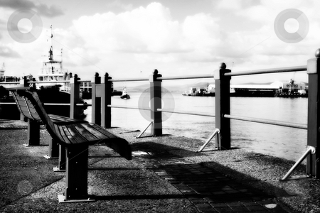 Benches at the harbour stock photo, Two red seats at the Cape Town Waterfront harbour in South Africa, with boats in the background on a cloudy day. Black and white, high contrast and defocussed by Sean Nel