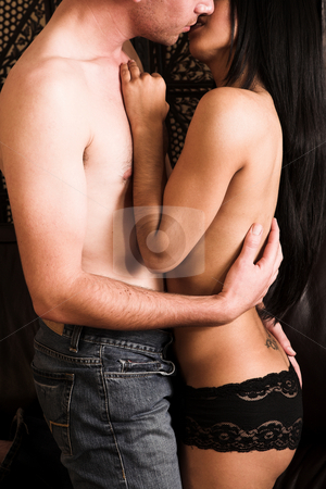 Lovers embrace stock photo, Multi-ethnic couple in passionate embrace and undressing each other in sexually active foreplay by Sean Nel