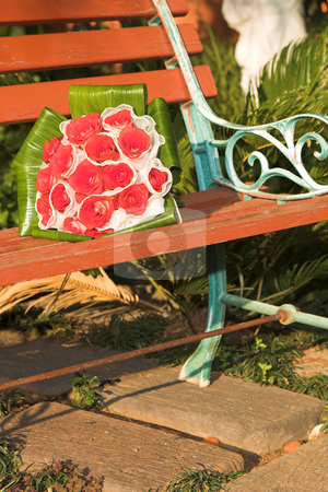 Wedding bouquet stock photo, Red rose wedding bouquet on a wooden bench in the garden draped in a white veil. Lying in the sunlight by Sean Nel