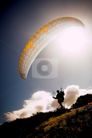 Paraglider launching from the mountain ridge stock photo, Paraglider launching from the ridge with a yellow and white canopy and the sun from behind. The paraglider is a silhouette and the shot is taken right after takeoff. The paraglider is sharp, with slight movement on the wing by Sean Nel
