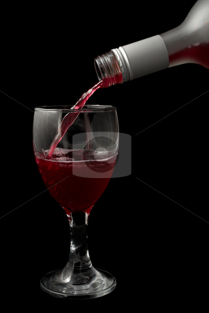 Wine and glass #1 stock photo, Wine is being poured into a glass - black background by Sean Nel